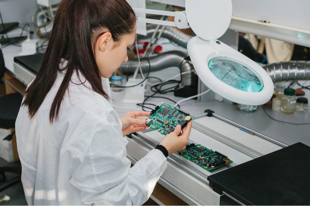 A woman assembling a circuit board.