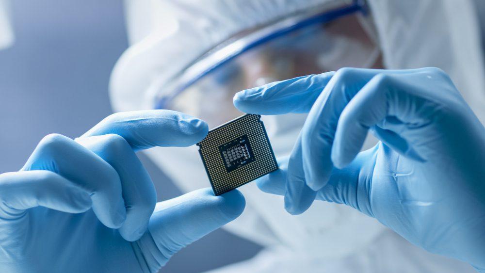 An electronics technician examining a microchip.