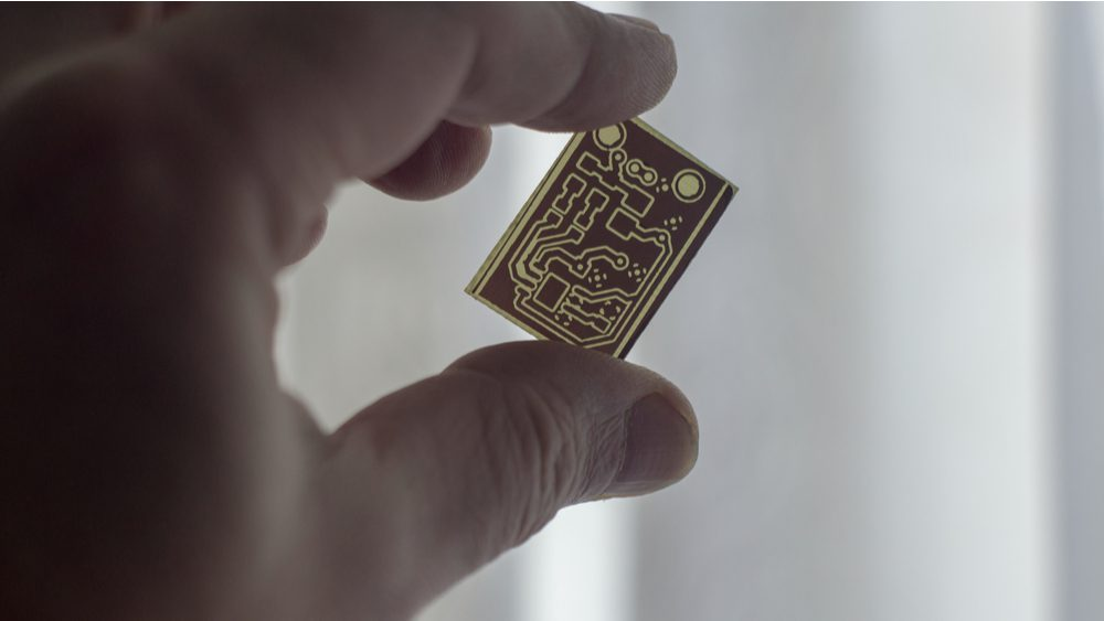 A small PCB held between two fingers