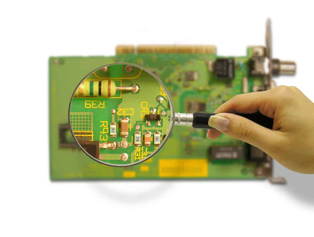 Person using a magnifying glass to look at a PCB